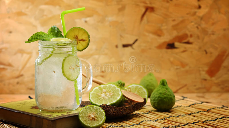 Kaffir lime So, Bergamot soda Cool drink, Thailand tradition Herb for Treatment of Acid Reflux, with Oriental Earth tone map backg. Round.Have some space for royalty free stock image