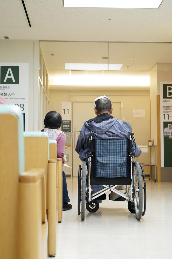 Old man sitting on wheelchair in hospital stock photos