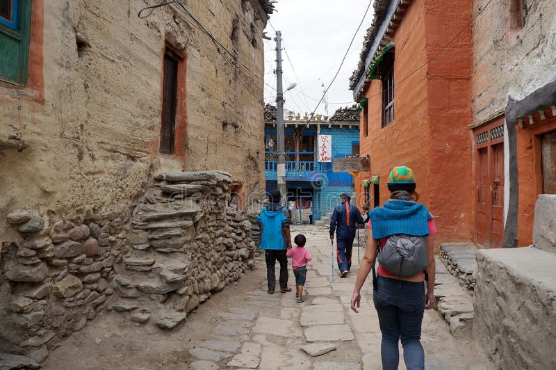 Locals and tourists walk along a narrow alley through the old town. Hike in the closed area of the upper Mustang. Nepal. Kagbeni, Mustang /Nepal - August 21 royalty free stock photo