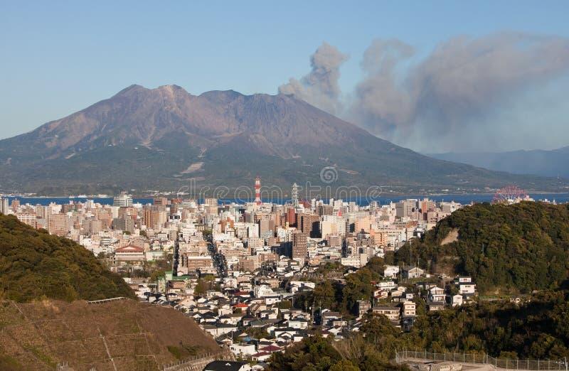 Kagoshima, Japão com montagem Sakurajima que entra em erupção imagem de stock