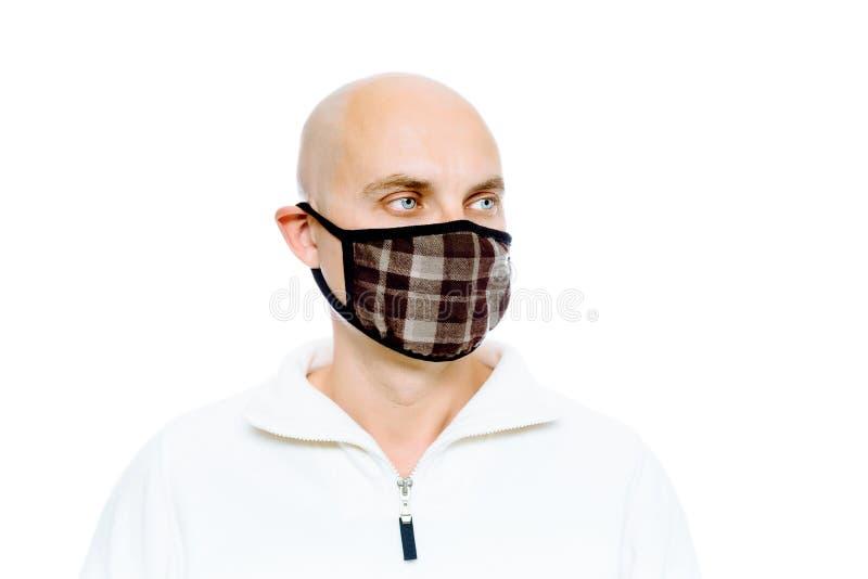 Kahl, Mann in einer weißen Jacke und Maske studio Getrennt stockfotos