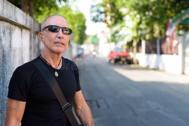 Kahler älterer touristischer denkender Mann beim Tragen von Sonnenbrille agains stockfotografie