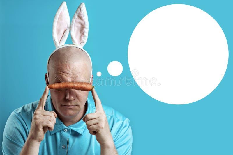 Kahler grober Mann in einem hellen Hemd und in den Häschenohren In den Händen von hält ihm eine Karotte, die Augen schließt stockfotos