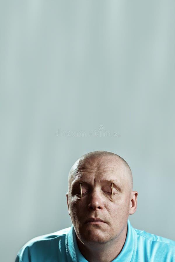 Kahler grober Mann in einem hellen T-Shirt setzte Match in seine Augen und in Schlaf ein lizenzfreie stockfotografie