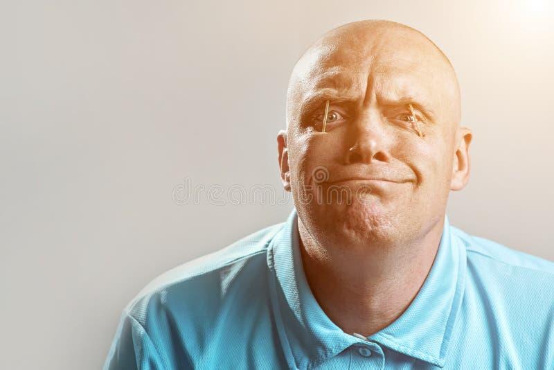Kahler grober Mann in einem hellen T-Shirt setzte Match in seine Augen und in Schlaf ein lizenzfreie stockbilder