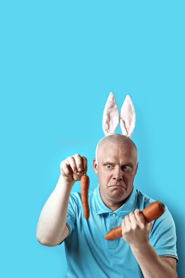 Kahler grober Mann im hellen T-Shirt und in den Hasenohren In seinen Händen hält er die Karotte einer anderen Größe stockfoto