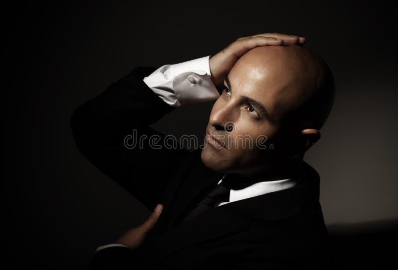 Kahler Mann, der schwarzen Anzug trägt stockfotografie