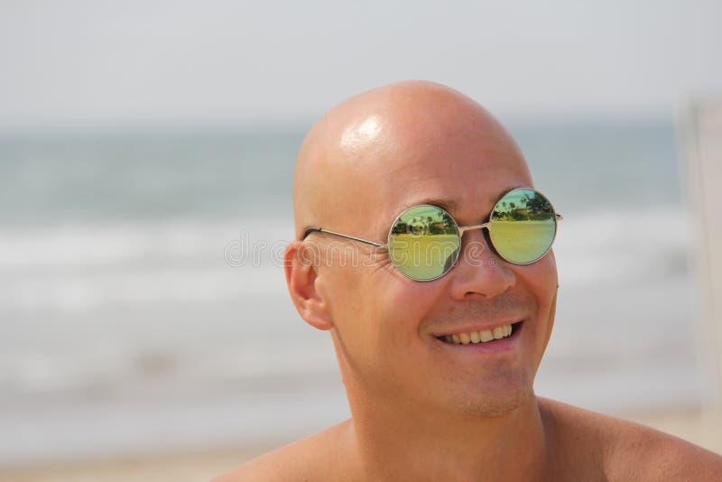 Kahler Mann in der Spiegelsonnenbrille Ein schöner gebräunter Mann im Urlaub, lächelnd Porträt einer Mannnahaufnahme Palmen und d lizenzfreie stockbilder