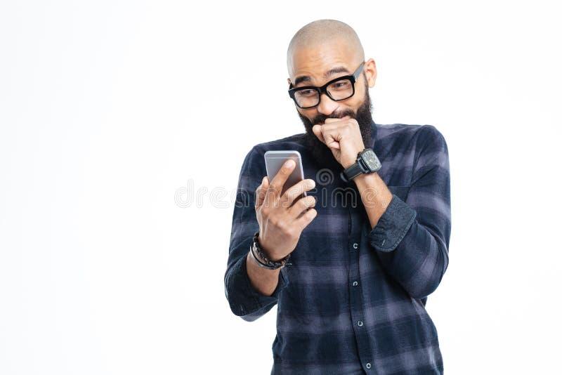 Kahler Mann des netten Afroamerikaners, der Smartphone und das Lachen verwendet stockfotografie