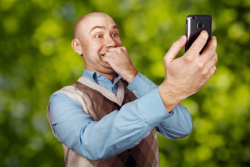 Kahler Mann des Porträts, der auf dem Telefon und dem selfie auf grünem bokeh Hintergrund spricht lizenzfreies stockbild