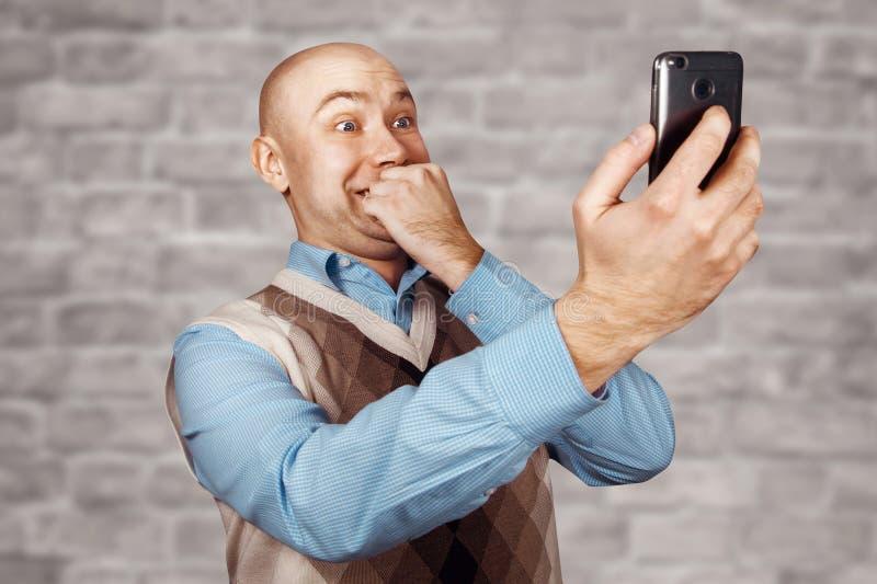 Kahler Mann des Porträts, der auf dem Telefon und dem selfie auf weißem Backsteinmauerhintergrund spricht stockbilder