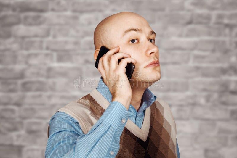 Kahler Mann des Porträts, der am Telefon auf weißem Backsteinmauerhintergrund spricht stockfotografie
