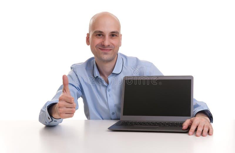 Kahler Mann mit dem Laptop, der sich seinen Daumen zeigt stockfotos
