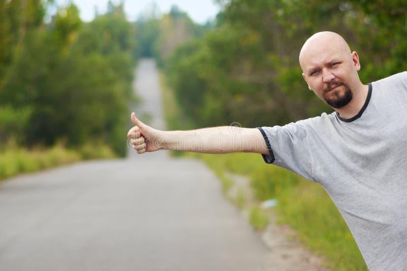 Kahlköpfiger Mann, der auf Straße hitching ist lizenzfreie stockbilder