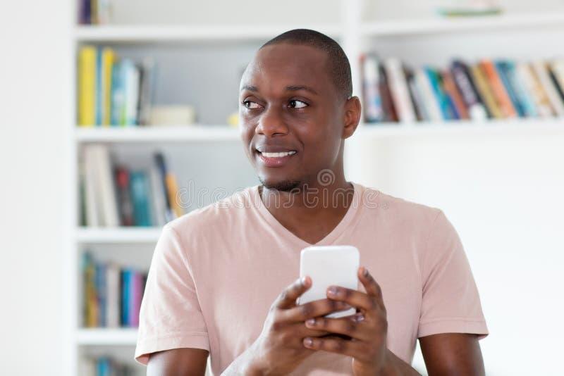 Kahlköpfiger reifer Mann des Afroamerikaners, der Mitteilung sendet stockbild