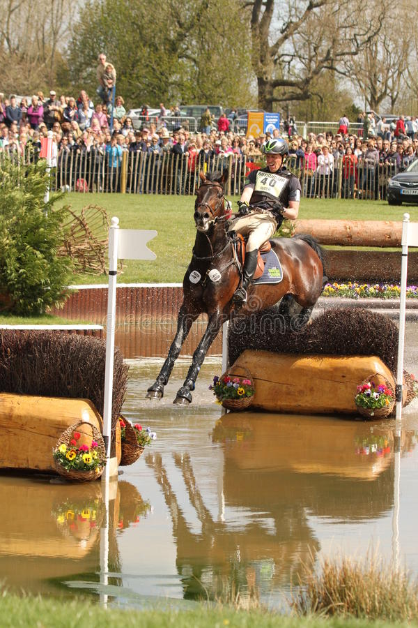 Kai Ruder jumping at the Lake. Kai Ruder and his horse LePrince Des Bois jump the skinny brush fence in the water at the Lake during the cross country phase of royalty free stock photo