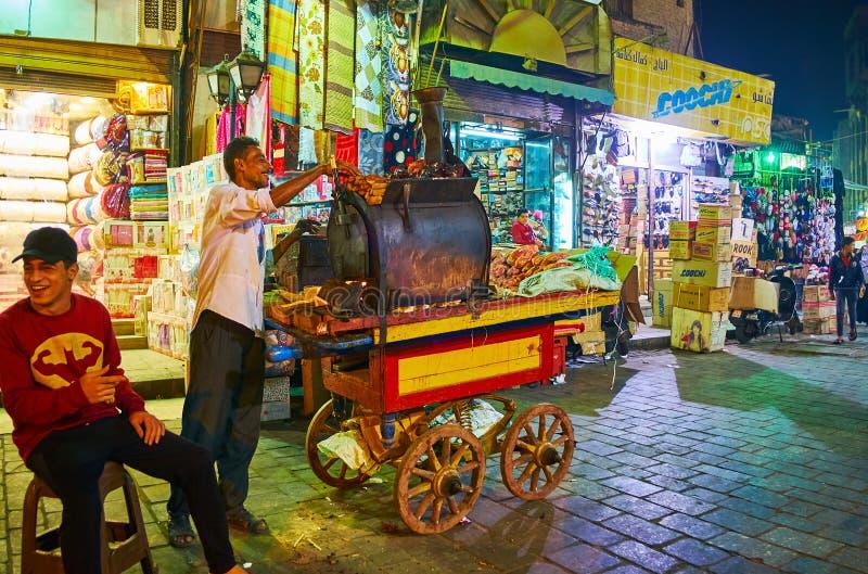 KAIR EGIPT, GRUDZIEŃ, - 21, 2017: Uliczny sprzedawca batat gotuje batata w piekarniku, stoi na jego karmowej furze w Al Muizz fotografia stock