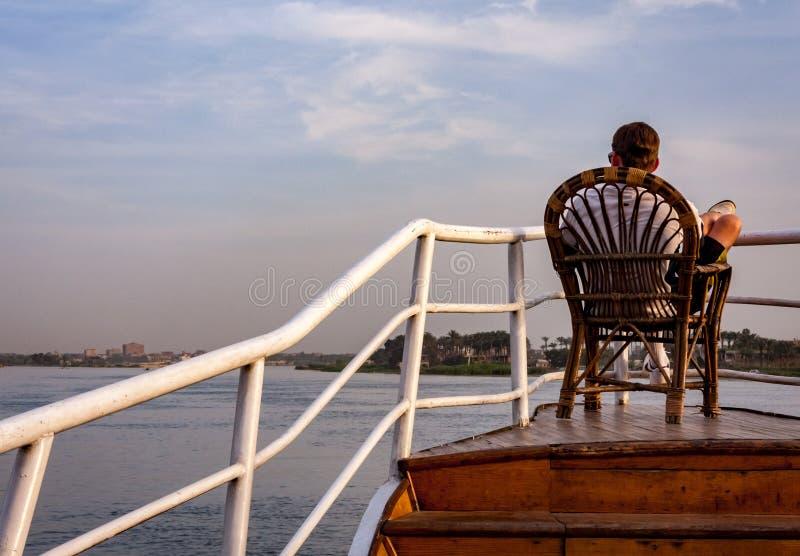 Kairo, Ägypten am 6. April 2012: Mann, der am Bogen des Segelboots auf dem Fluss Nil in Kairo sich entspannt stockbilder