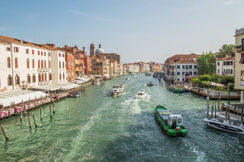 Kaj av en storslagen kanal med lastfartyg, flodspårvagnar, fartyg Längs kanalen finns det Venetian hus arkivfoto