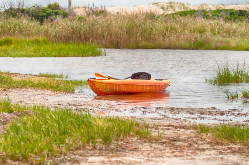 Kajak arancio sulla spiaggia del suono di pamlino immagine stock