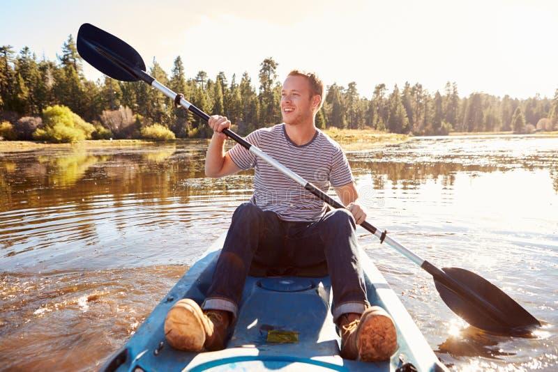 Kajak del rowing del hombre joven en el lago imagen de archivo