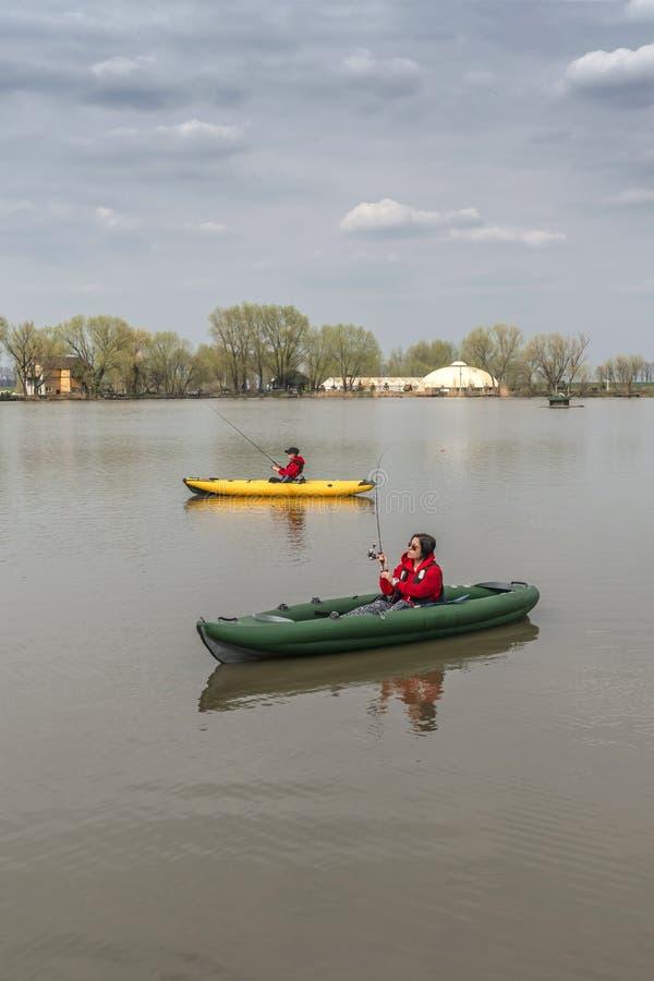 Kajak die bij meer vissen Twee vissters op inflateble boten met stock afbeeldingen