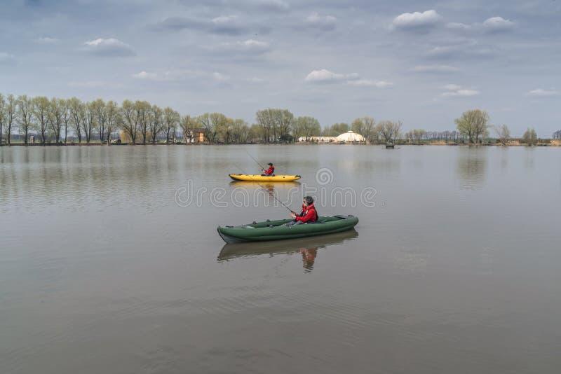 Kajak die bij meer vissen Twee vissters op inflateble boten met royalty-vrije stock foto's