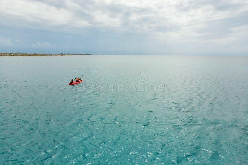 Kajak en el mar de la vista posterior Pares felices kayaking a lo largo del horizonte con las nubes hermosas El viajar, nuevo foto de archivo
