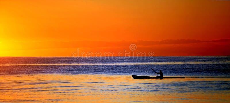 Kajak en el océano en la puesta del sol imagenes de archivo