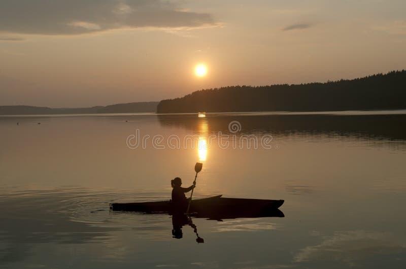 Kajak en la puesta del sol fotografía de archivo