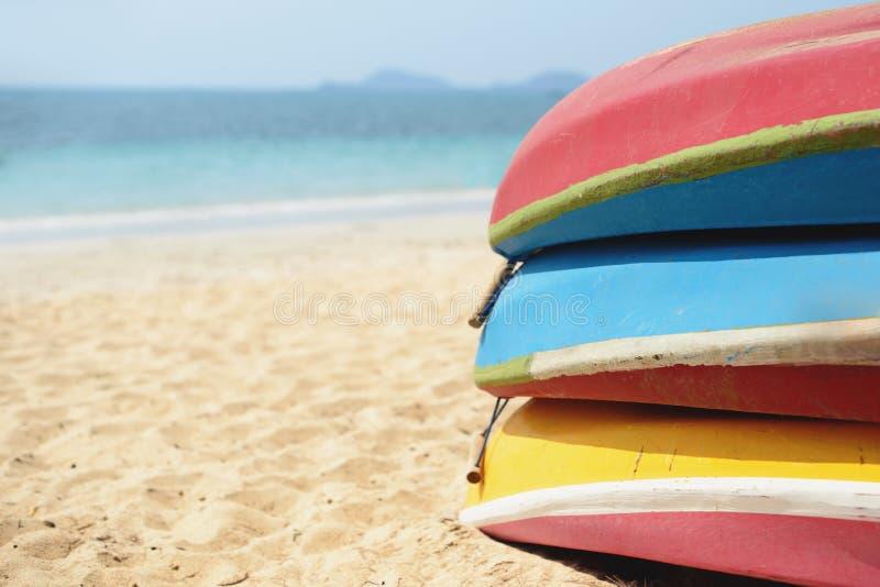 Kajak impilati sulla spiaggia di sabbia Barche variopinte davanti alla costa di mare fotografia stock