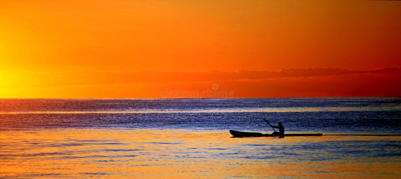 Kajak in oceaan bij zonsondergang stock afbeeldingen