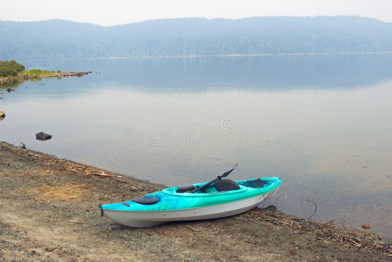 Kajak på en strand av sjön i campingplats arkivfoto