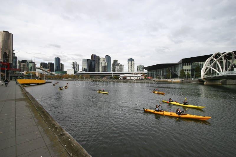 Kajak Paddlers auf Yarra-Fluss, Südkai, Melbourne, Victoria, Australien Promenade mit Küstenstadtbild von Wolkenkratzern stockfotografie