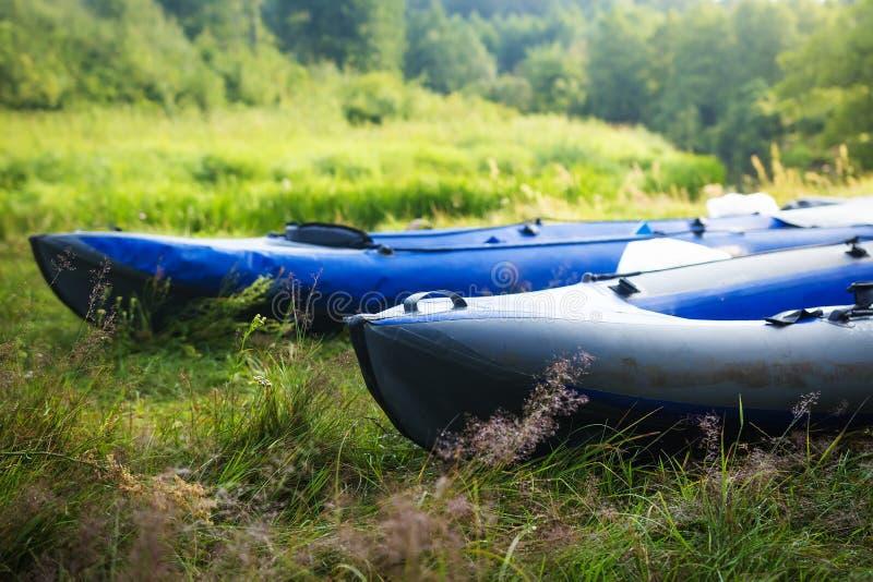 Kajak sull'erba sulla sponda del fiume Barche o canoe fotografia stock