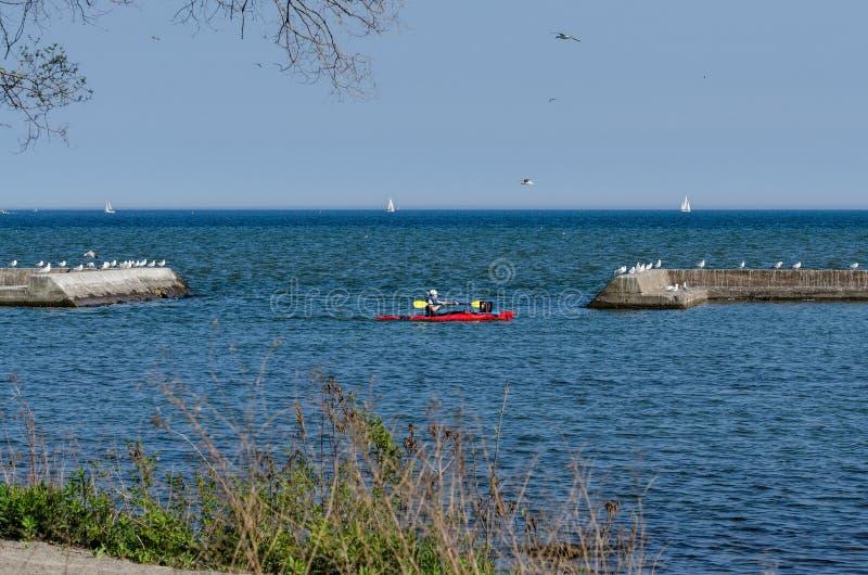 Kajak und Segelboote auf einem See lizenzfreie stockbilder