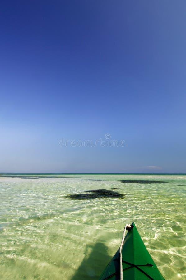 Kajak verde que flota en el agua verde clara con los cielos azules de cobalto foto de archivo