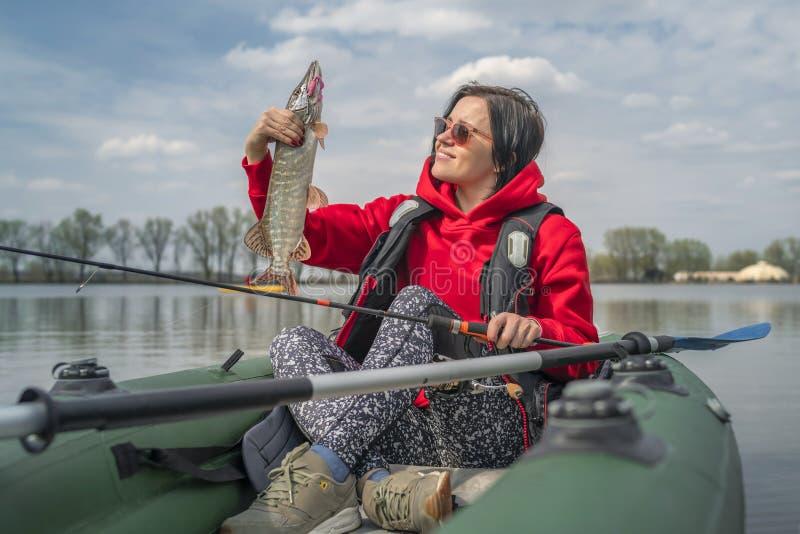 Kajak visserij De de holdingssnoeken van het vissersmeisje vissen trofee op opblaasbare boot met vistuig bij meer stock foto's