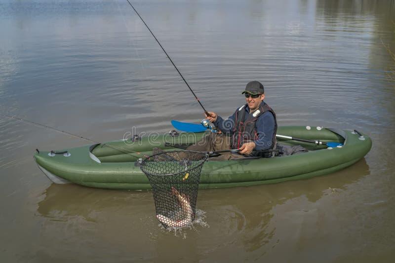 Kajak visserij Visser gevangen snoekenvissen op opblaasbare boot met vistuig bij meer royalty-vrije stock fotografie