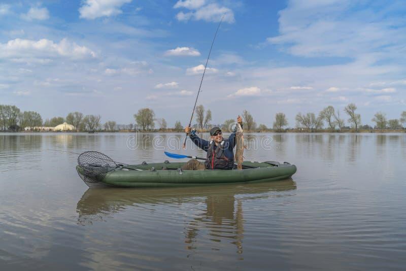 Kajak visserij Visser gevangen snoekenvissen op opblaasbare boot met vistuig bij meer royalty-vrije stock afbeeldingen