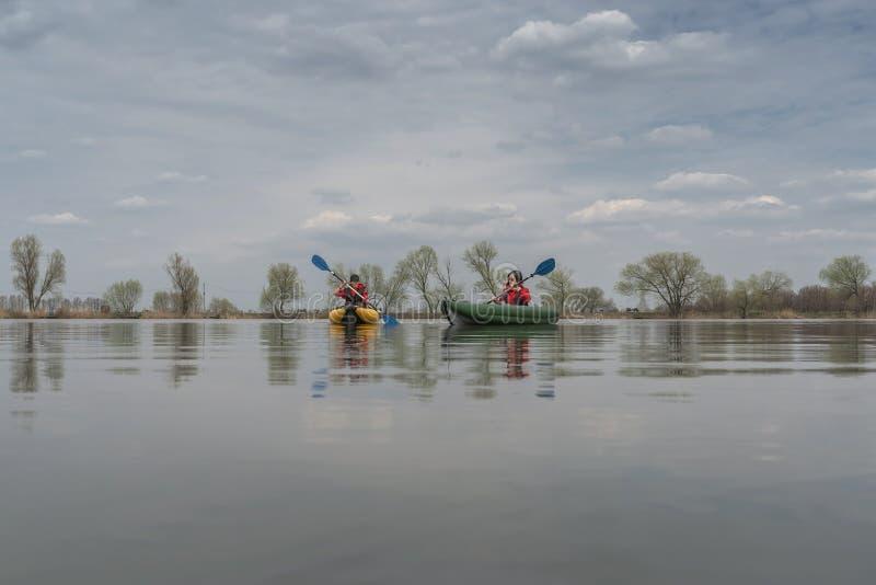 Kajaka po??w przy jeziorem Dwa rybaczki na nadmuchiwanych łodziach z połowu sprzętem fotografia royalty free