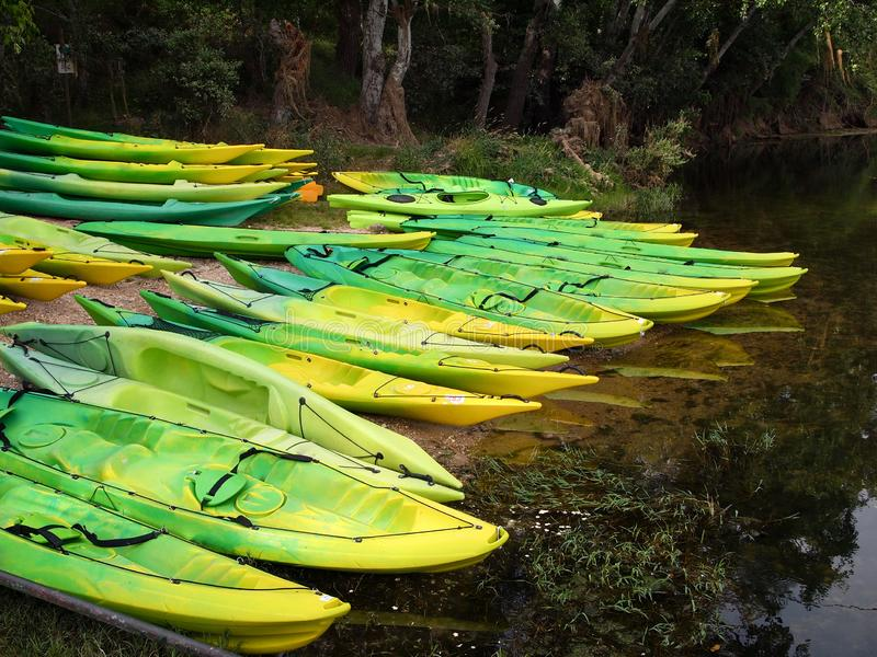 Kajaker och kanoter på flodbanken arkivfoto