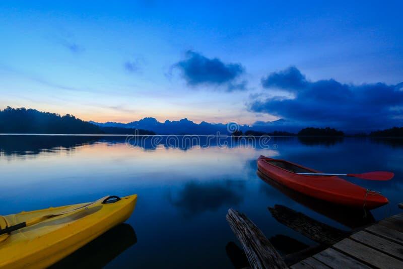 Kajakfartyg på sjön med härlig skymninghimmel royaltyfri foto