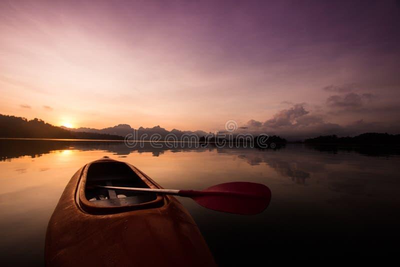 Kajakfartyg på sjön med härlig solnedgångplats fotografering för bildbyråer