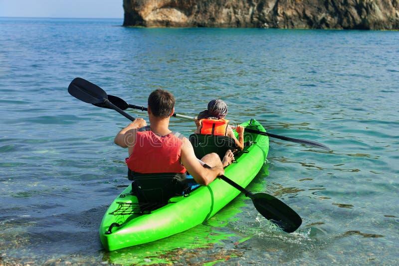 kajaki Dobiera się kanoeing w morzu blisko wyspy z górami Ludzie kayaking w oceanie obraz stock