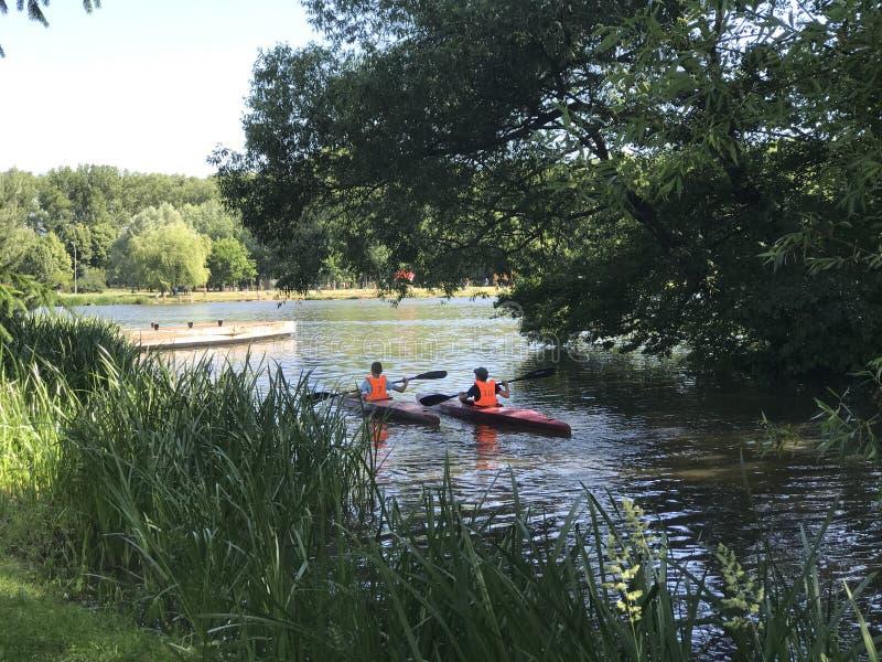 Kajakrodd Barn i lifejackets seglar med kanoten längs kanalen i parkera arkivbild