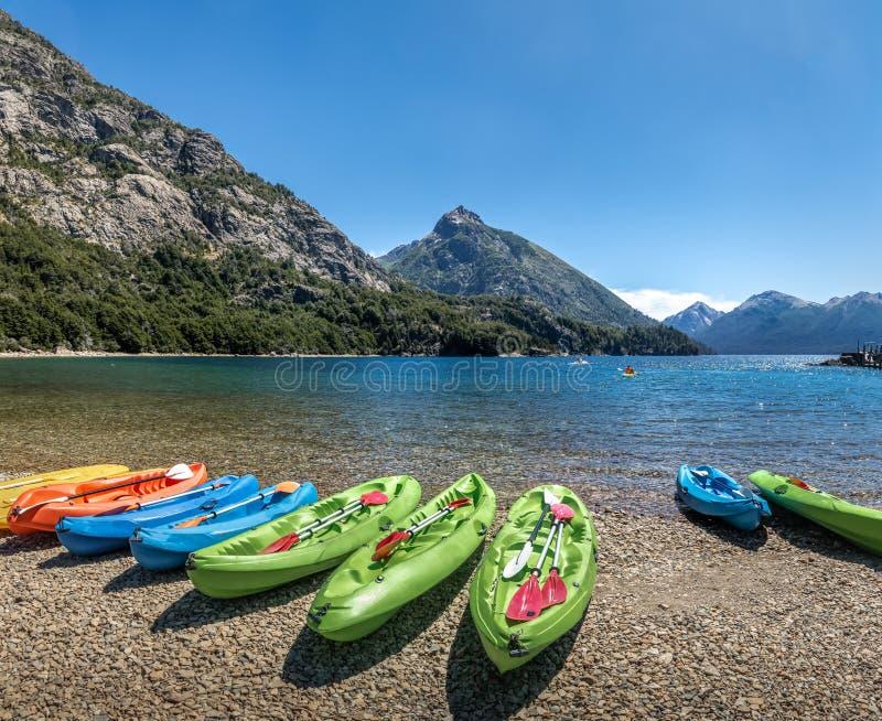 Kajaks coloridos en un lago rodeado por las montañas en Bahia Lopez en Circuito Chico - Bariloche, Patagonia, la Argentina fotografía de archivo libre de regalías