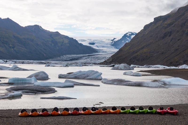 Kajaks delante de la laguna del glaciar de Heinabergsjokull foto de archivo