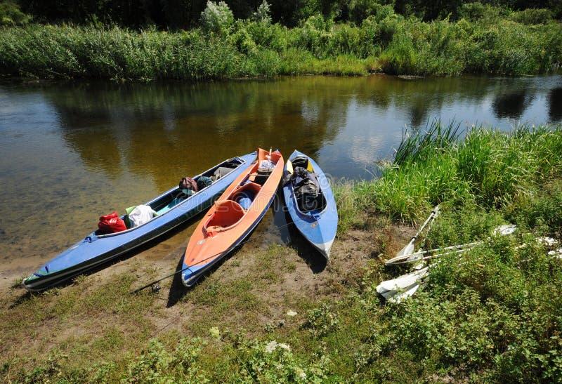 3 kajaks op de bank van een kleine rivier in de zomer royalty-vrije stock foto's
