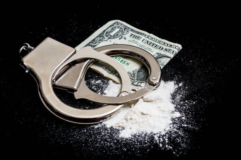 Kajdanki, pieniądze i leki na czarnym tle, zdjęcia royalty free